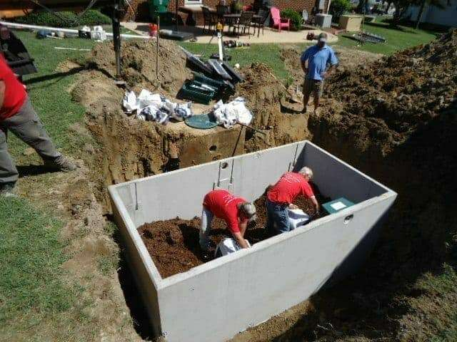 Miller's workers installing a septic tank