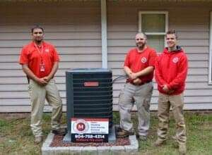 Miller's employees standing next to outdoor HVAC unit